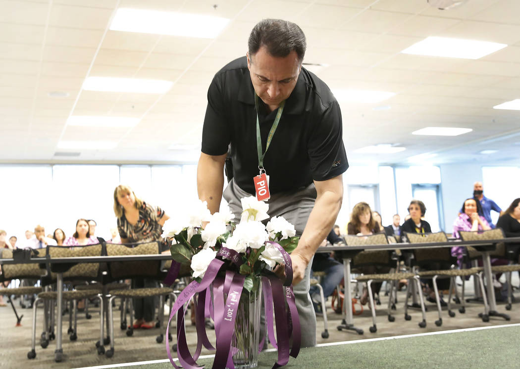 Jay Rivera of Metropolitan Police Department places a rose at the Metro headquarters on Wednesday Sept. 27, 2017, during the annual ceremony to remember victims of domestic violence. Bizuayehu Tes ...