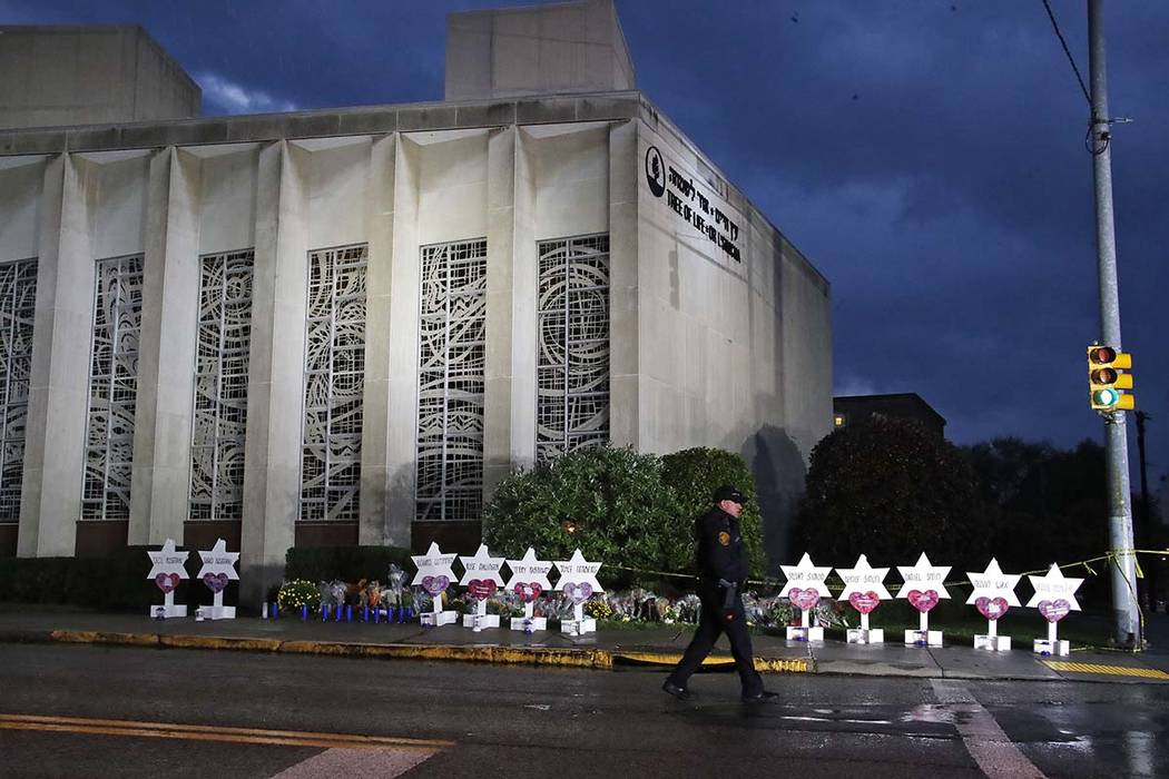 A Pittsburgh police officer walks past memorials at the Tree of Life Synagogue on Sunday in remembrance of those killed and injured when a shooter opened fire during services Saturday at the synag ...