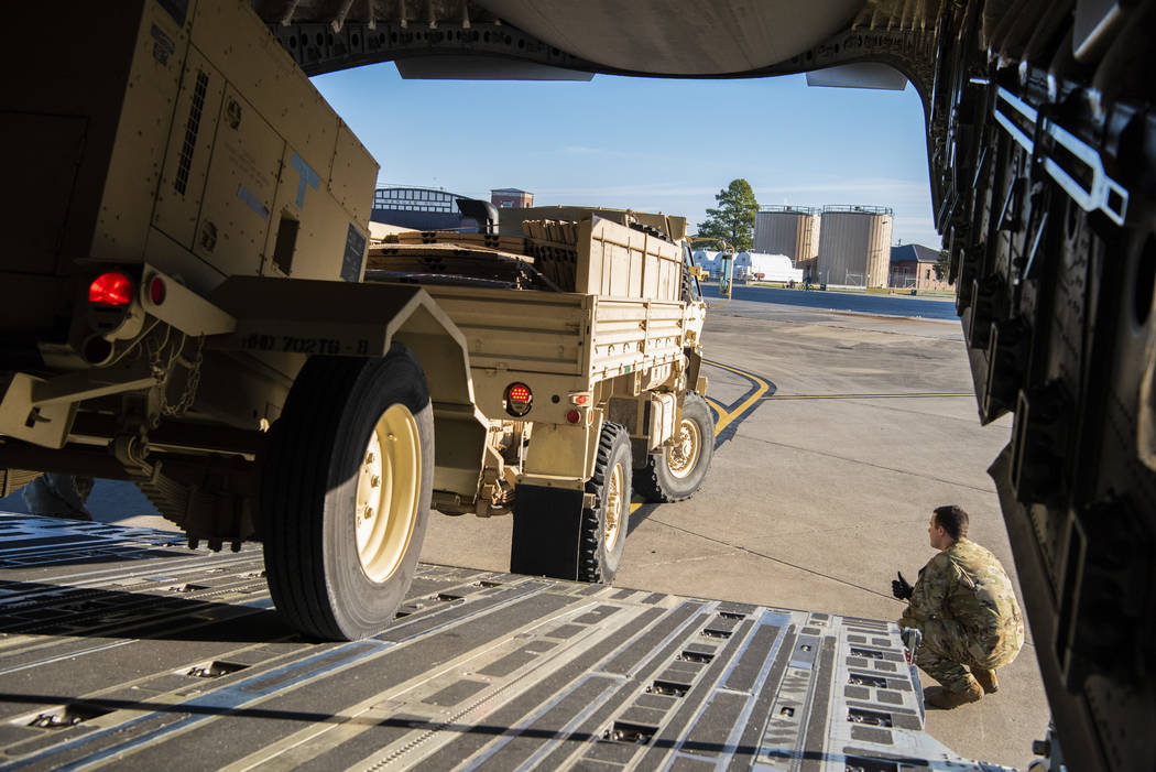 Airman 1st Class Trevor Pearce helping guide a military vehicle into the cargo compartment of a C-17 Globemaster III at Fort Knox, Kentucky, Oct. 29, 2018. The aircrews provided strategic airlift ...