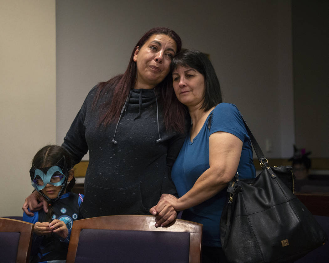 Dawn Hentzi stands by new adopted family member Ammerah, 6, and friend Patty Celis as they are sworn in by District Court Family Judge Cynthia Giuliani at Family Court in Las Vegas, Wednesday, Oct ...