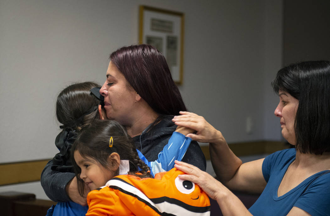 Dawn Hentzi holds her new adopted family member Ammerah, 6, while standing next to her other daughter Elia Raymond, 3, and her friend Patty Celis as they are sworn in by District Court Family Judg ...