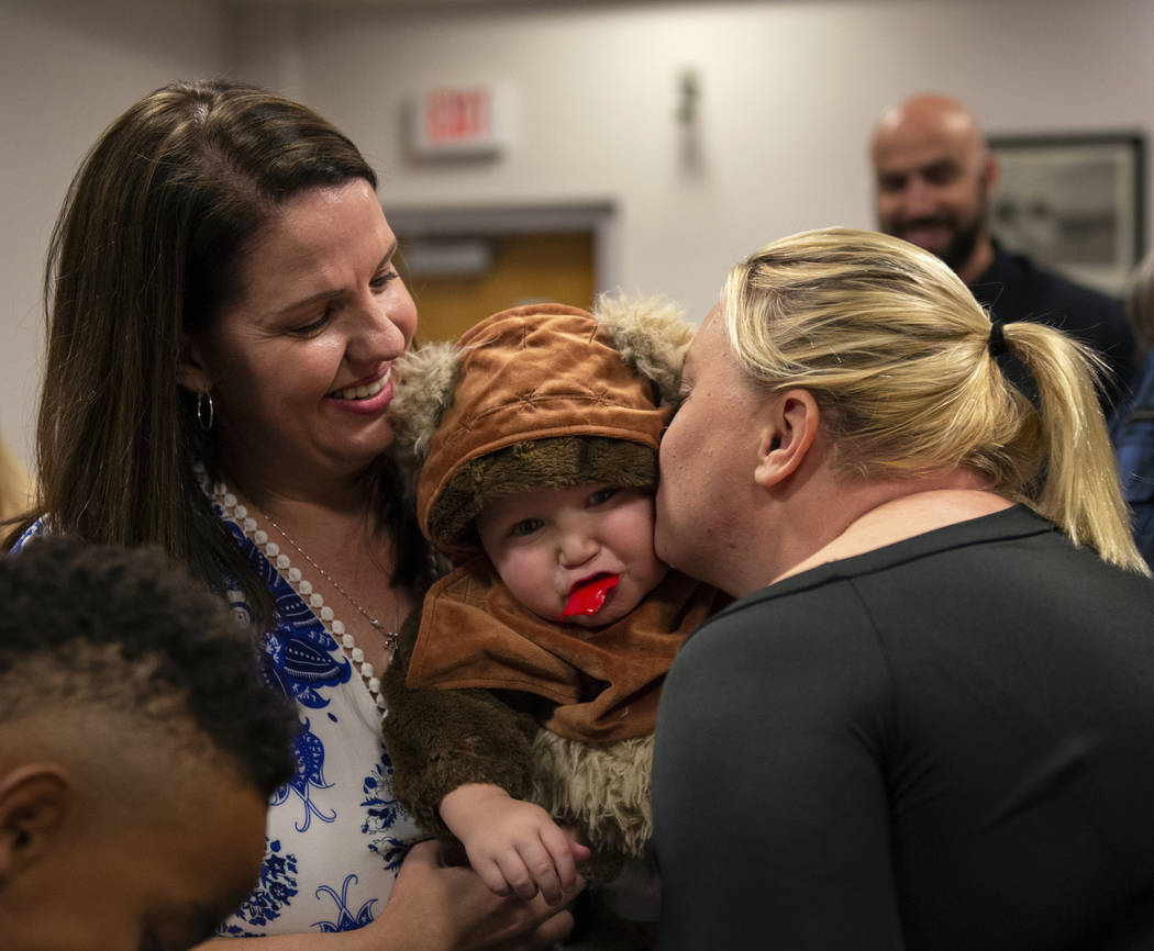 Julie Elliott holds new adopted family member Connor, 1, as Kim Forgione kisses him after they are sworn in by District Court Family Judge Cynthia Giuliani at Family Court in Las Vegas, Wednesday, ...