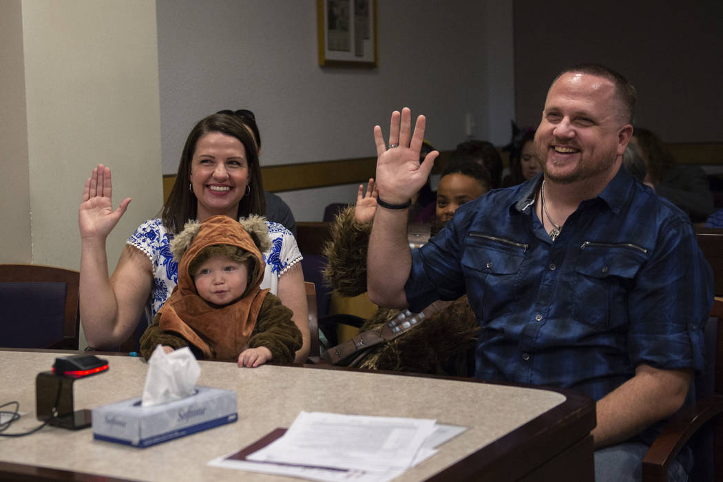 Julie Elliott and Keith Elliott raise their hands as they swear in new adopted family member Connor, 1, by District Court Family Judge Cynthia Giuliani at Family Court in Las Vegas, Wednesday, Oct ...