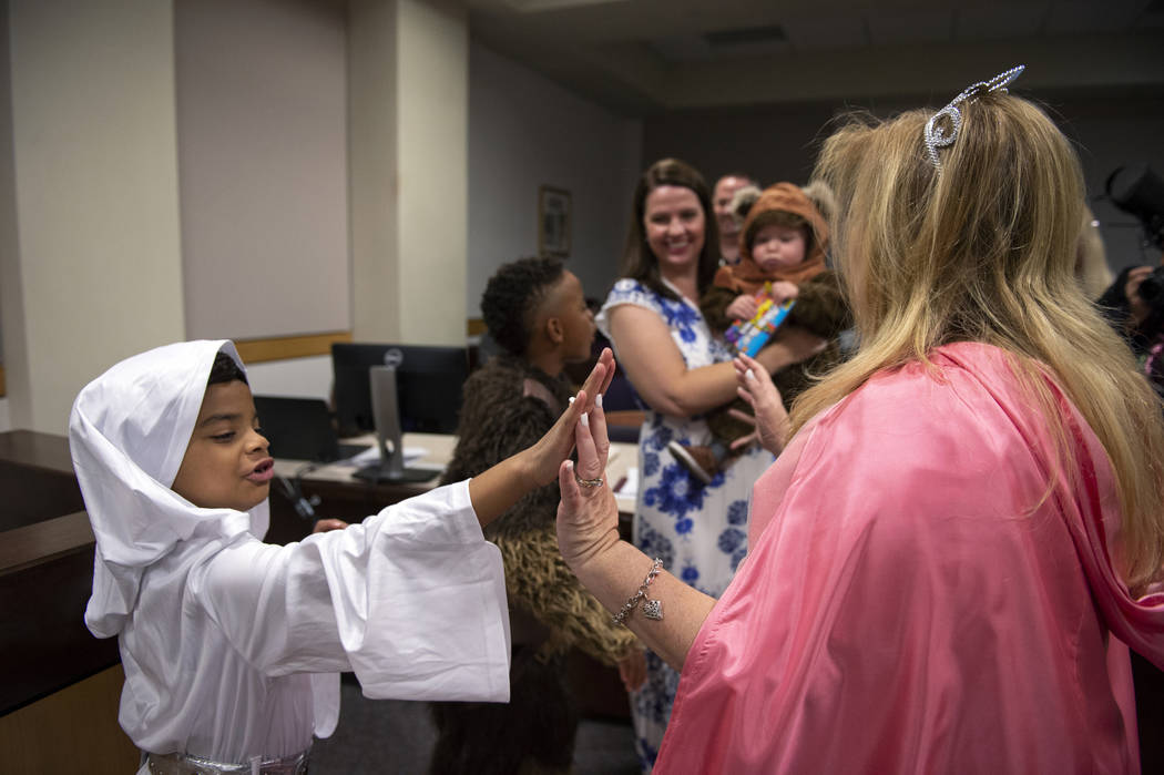 Jaelyn Elliott, 7, high fives District Court Family Judge Cynthia Giuliani after swearing in her new adopted family member Connor, 1, at Family Court in Las Vegas, Wednesday, Oct. 31, 2018. Caroli ...