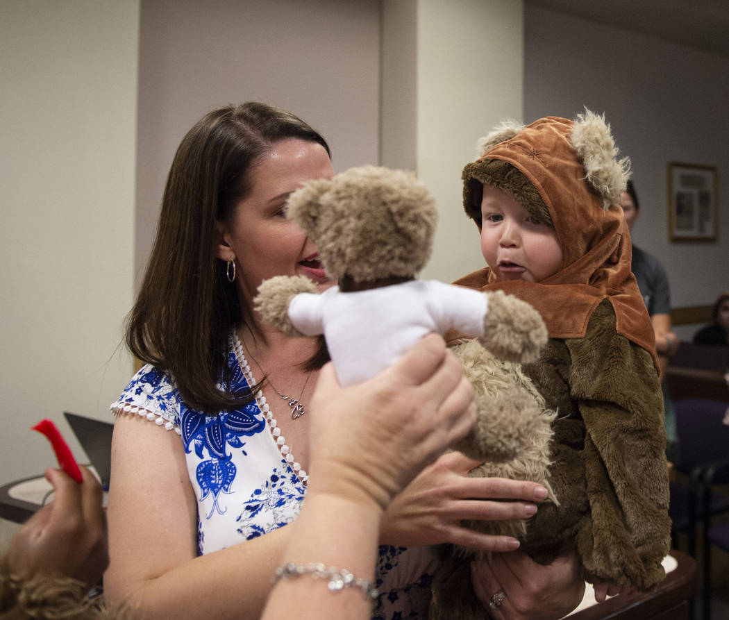 Julie Elliott holds new adopted family member Connor, 1, while District Court Family Judge Cynthia Giuliani holds out a teddy bear at Family Court in Las Vegas, Wednesday, Oct. 31, 2018. Caroline ...