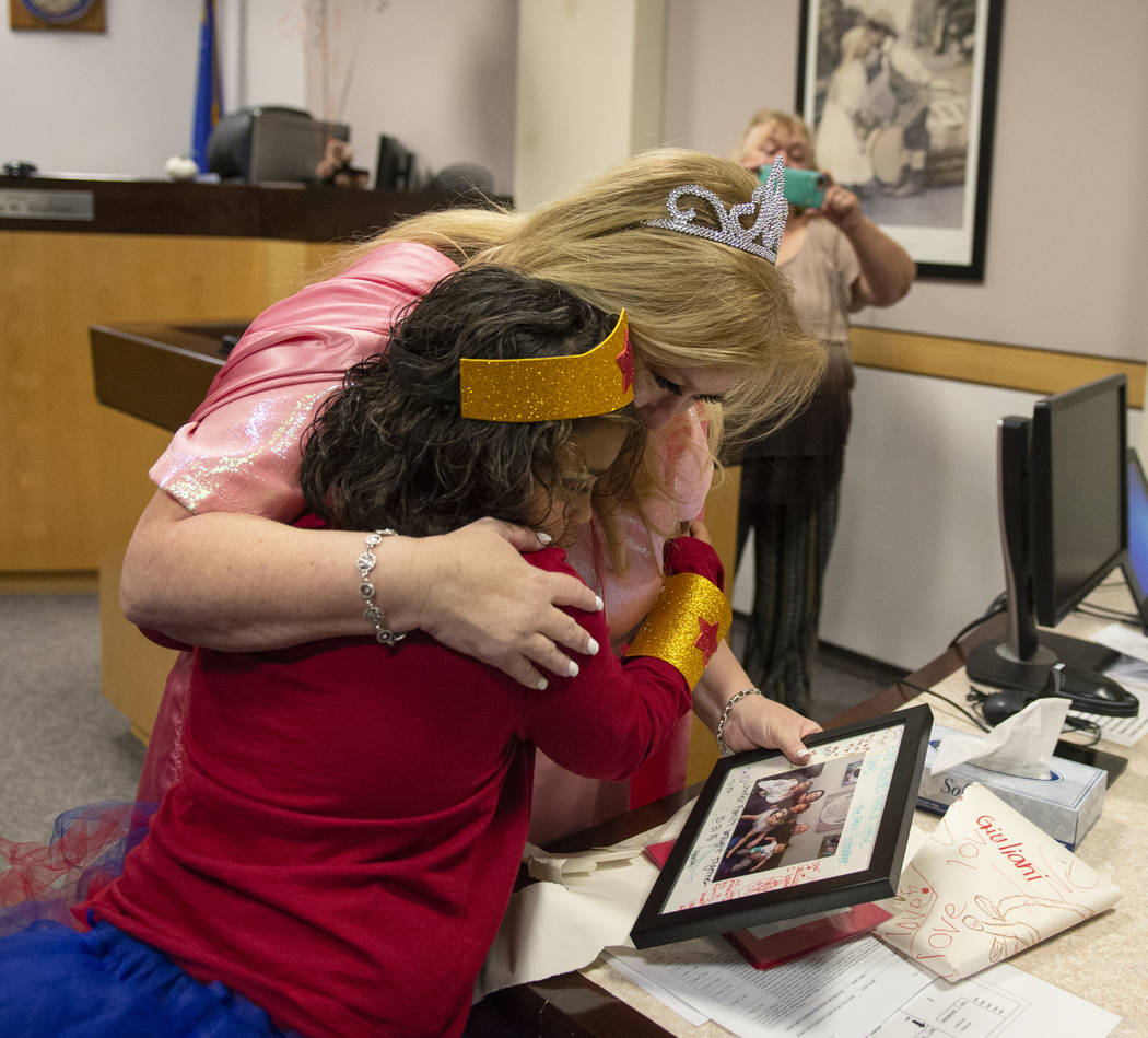 District Court Family Judge Cynthia Giuliani hugs Adilyn Lawter, 8, as she receives a gift from the Lawter family after finalizing the adoption process with her new family at Family Court in Las V ...