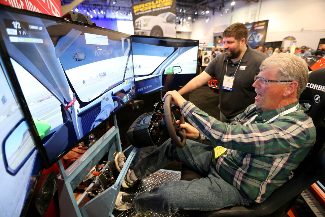 Gary Peltzer of Scottsdale, Ariz., drives a simulator with the help of Zach Davis at the Power Stop Performance Upgrade Brake Kits booth at the Specialty Equipment Market Show at the Las Vegas Con ...