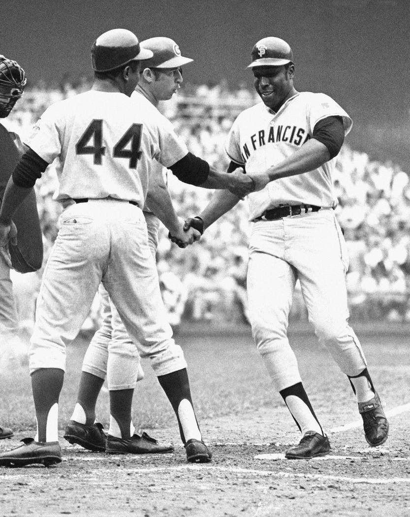 The National League's Willie McCovey of San Francisco is congratulated on crossing home in the third inning of the baseball All-Star Game in Washington after hitting in Hank Aaron (44) in Washingt ...