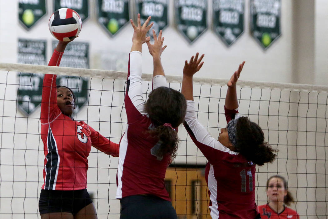 Las Vegas High School's Rimonee Wright sets the ball over the net as Cimarron Memorial High School's Natasha Obradovic, left, and Alexis Eager jump up to block the shot at the Summerlin Center in ...