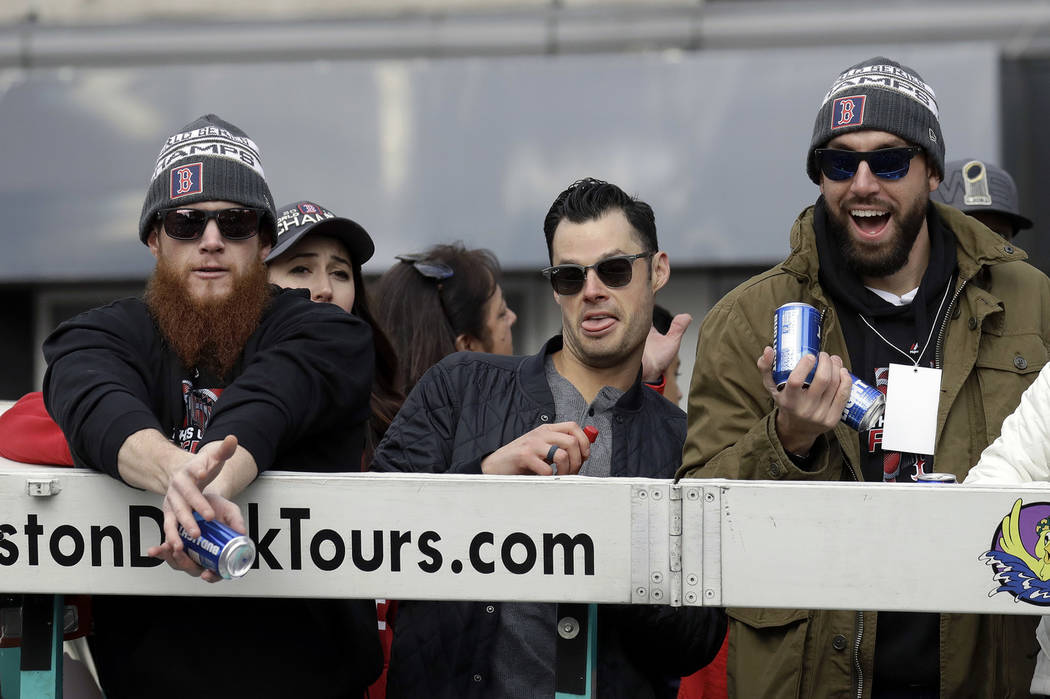 Boston Red Sox's Craig Kimbrel, left, Joe Kelly, center, and Matt Barnes catch beer cans tossed during a parade to celebrate the team's World Series championship over the Los Angeles Dodgers, Wedn ...