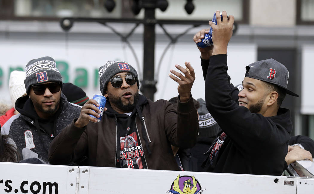 Boston Red Sox's Xander Bogaerts, left, Eduardo Nunez, center, and Eduardo Rodriguez catch beer cans tossed from the crowd during a parade to celebrate the team's World Series championship over th ...