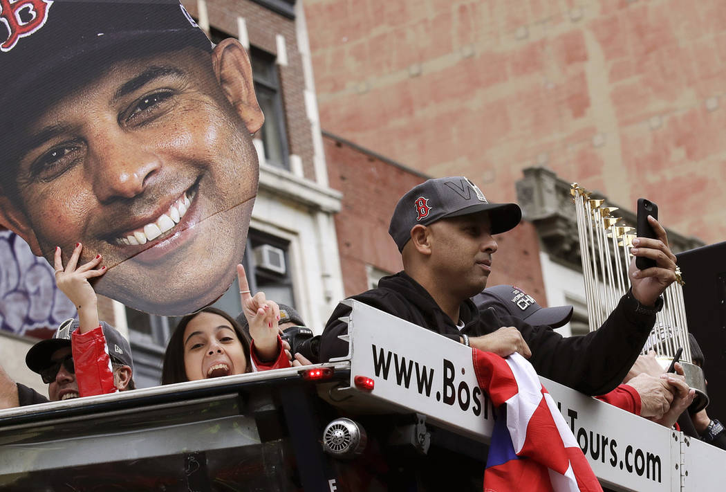 Boston Red Sox manager Alex Cora takes a photo as his daughter Camila, left, holds a cutout photo of him during a parade to celebrate the team's World Series championship over the Los Angeles Dodg ...