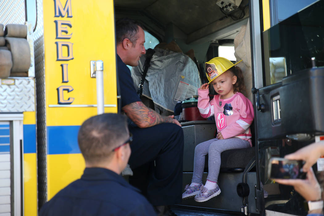 Scarlett Mize, 3, sits inside a fire engine with Clark County Fire Department firefighter Jonathan McBreen during a fire awareness visit to Merryhill Preschool, 5055 S. Durango Dr., in Las Vegas, ...