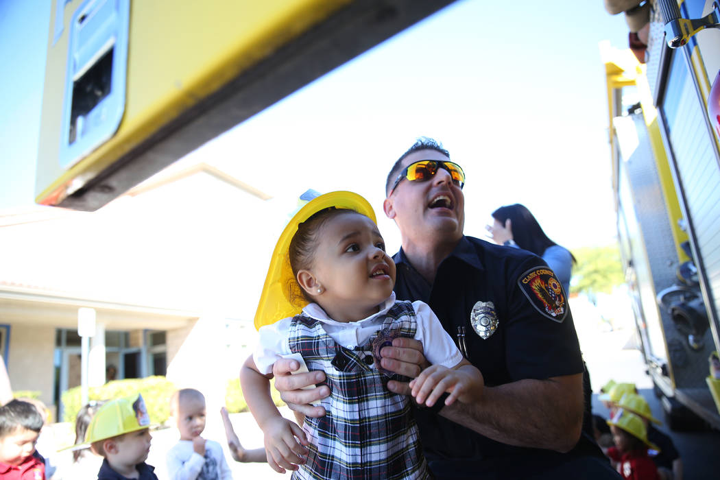 Clark County Fire Department Firefighter Adam Smith carries Giovanna McMurry, 3, into a fire engine during a fire awareness visit to Merryhill Preschool, 5055 S. Durango Dr., in Las Vegas, Wednesd ...