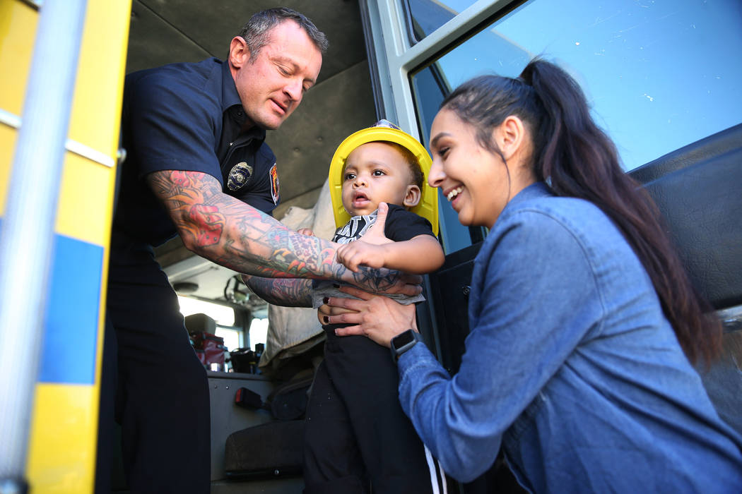 Clark County Fire Department firefighter Jonathan McBreen, left, after showing Avery Duncan, 1, inside a fire engine with infant co-lead Felecia Esparza, during a fire awareness visit to Merryhill ...