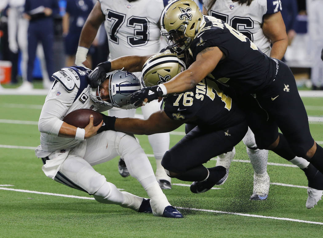Dallas Cowboys quarterback Dak Prescott (4) is sacked by New Orleans Saints defensive tackle Taylor Stallworth (76) during the second half of an NFL football game, in Arlington, Texas, Thursday, N ...