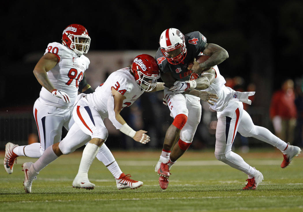 New Mexico quarterback Sheriron Jones (4) is stopped by Fresno State defensive end Mykal Walker, right, and linebacker George Helmuth (34) during the first half of an NCAA college football game in ...