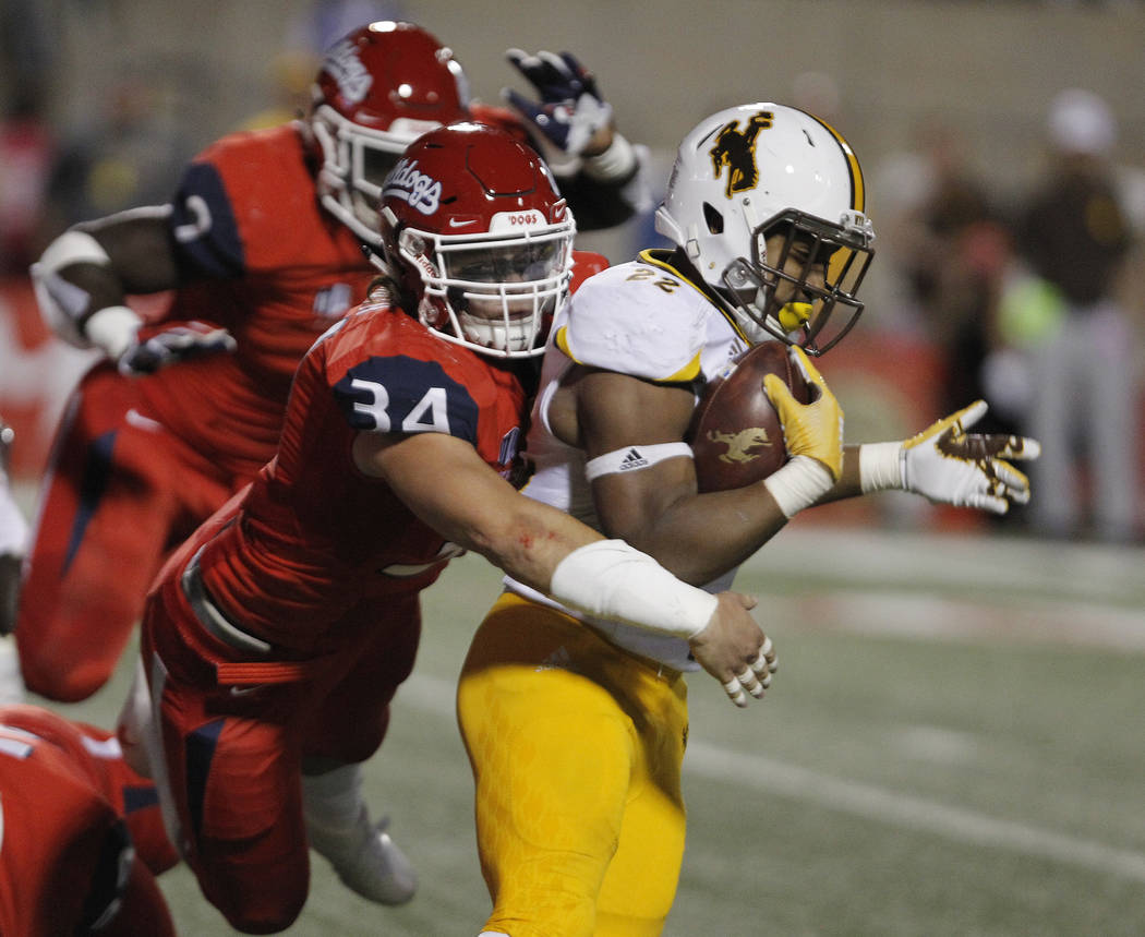 Wyoming running back Nico Evans is tackled by Fresno State linebacker George Helmuth during the first half of an NCAA college football game in Fresno, Calif., Saturday, Oct. 13, 2018. (AP Photo/Ga ...