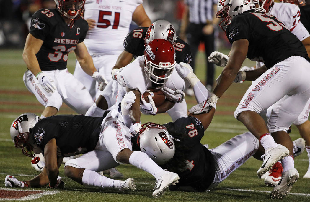 Fresno State Bulldogs running back Dejonte O'Neal, center, is tackled by UNLV Rebels defensive lineman Kolo Uasike (94) after a gain during the first half of an NCAA college football game Saturday ...