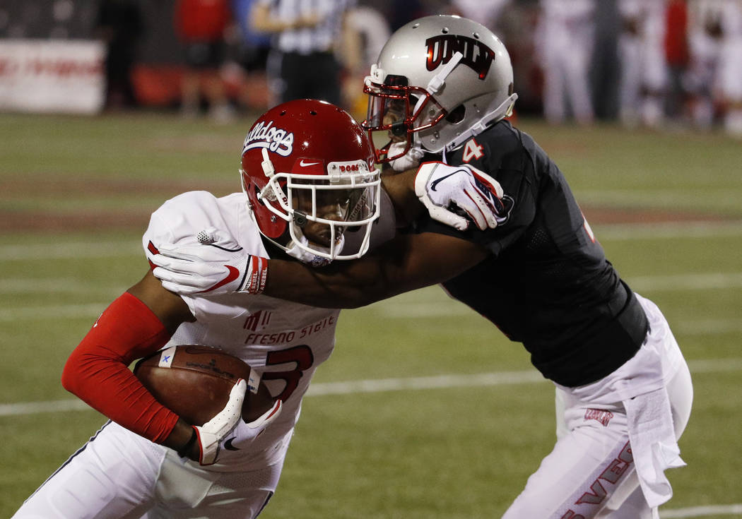 UNLV Rebels defensive back Alex Perry (4) tackles Fresno State Bulldogs wide receiver KeeSean Johnson (3) during the first half of an NCAA college football game Saturday, Nov. 3, 2018, in Las Vega ...