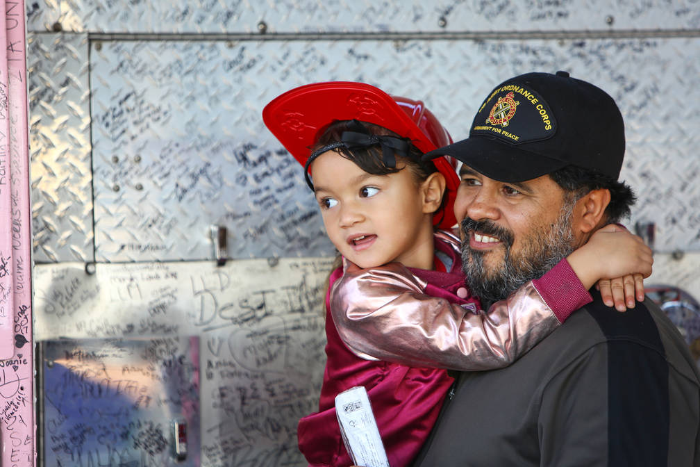 Oscar Smith holds his daughter, Elala Smith, 4, in front of a retired North Las Vegas Fire Department fire truck painted pink and covered with signatures to raise breast cancer awareness at the 4t ...