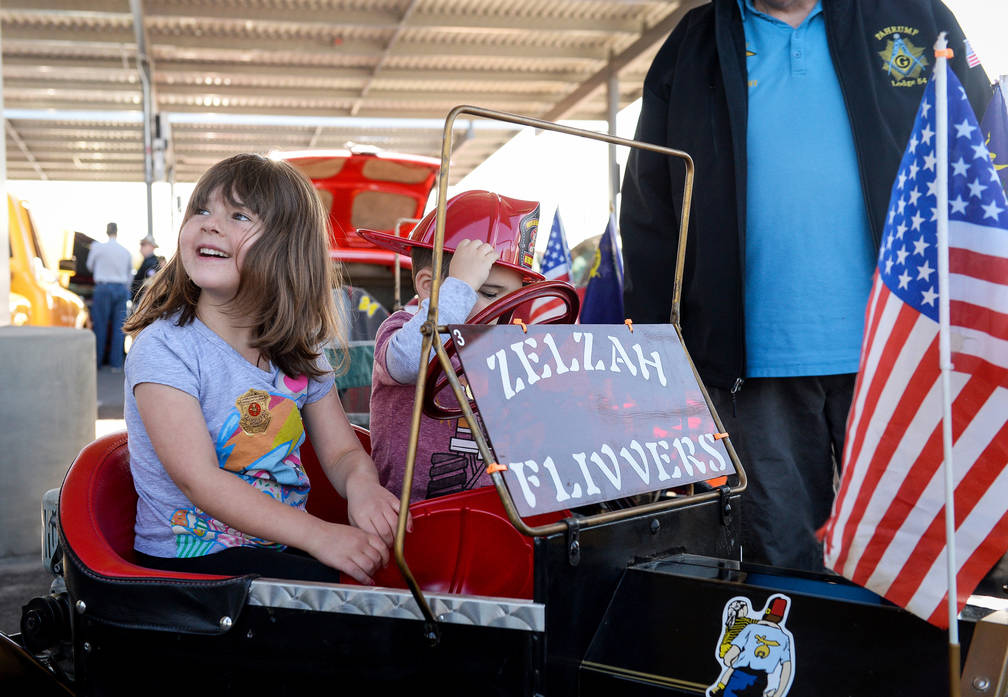 Amelia Shay, 4, and Lennon Shay, 2, from Las Vegas sit in one of the Shrine Flivvers' miniature cars at the 4th Annual Veterans Day Car Show and BBQ in celebration of Veterans Day at the VA Southe ...