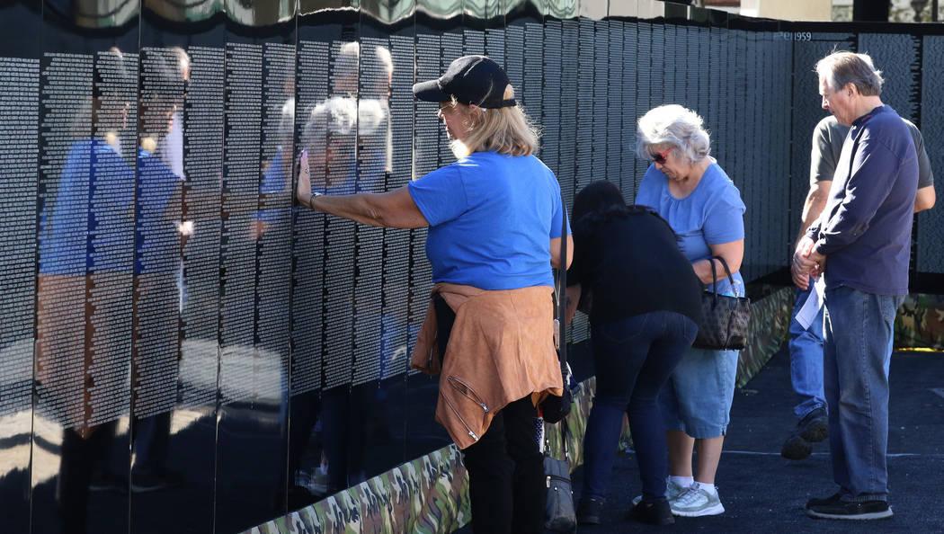 People, including Cathy Marvin, left, visit a half-size replica of the Vietnam Veterans Memorial wall on Friday, Nov. 2, 2018, in Las Vegas. (Bizuayehu Tesfaye/Las Vegas Review-Journal) @bizutesfaye