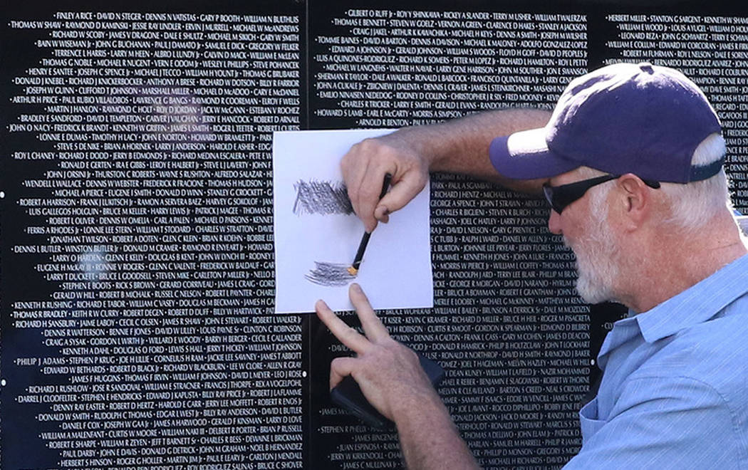 Carl Adelhock makes a rubbing on killed soldier name as he visits a half-size replica of the Vietnam Veterans Memorial wall on Friday, Nov. 2, 2018, in Las Vegas. (Bizuayehu Tesfaye/Las Vegas Revi ...