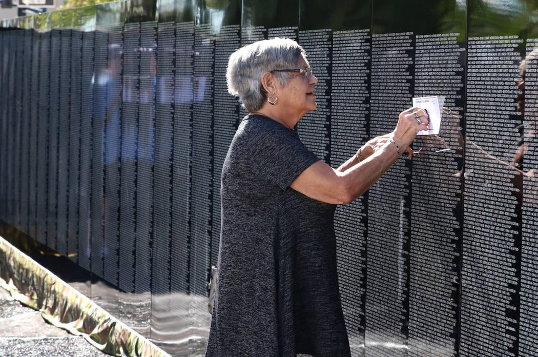 Kathy Perkins makes a rubbing on killed soldier name as she visits a half-size replica of the Vietnam Veterans Memorial wall on Friday, Nov. 2, 2018, in Las Vegas. (Bizuayehu Tesfaye/Las Vegas Rev ...