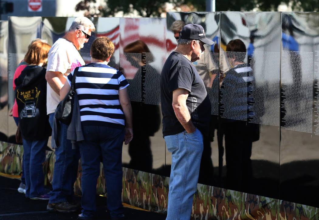 People, including Vietnam Marine Corps Veteran James Lawrence, second left, visit a half-size replica of the Vietnam Veterans Memorial wall on Friday, Nov. 2, 2018, in Las Vegas. (Bizuayehu Tesfay ...
