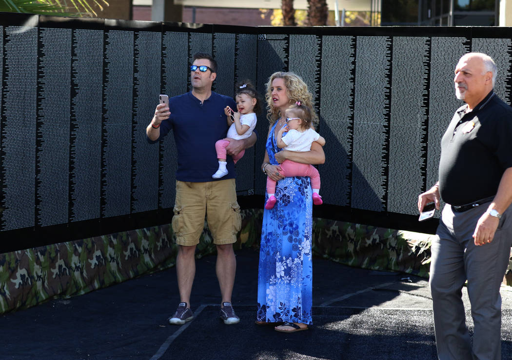 Brian Cook, left, visits a half-size replica of the Vietnam Veteran's Memorial wall with his daughter Violte, his wife Michelle and daughter Faith on Friday, Nov. 2, 2018, in Las Vegas. (Bi ...
