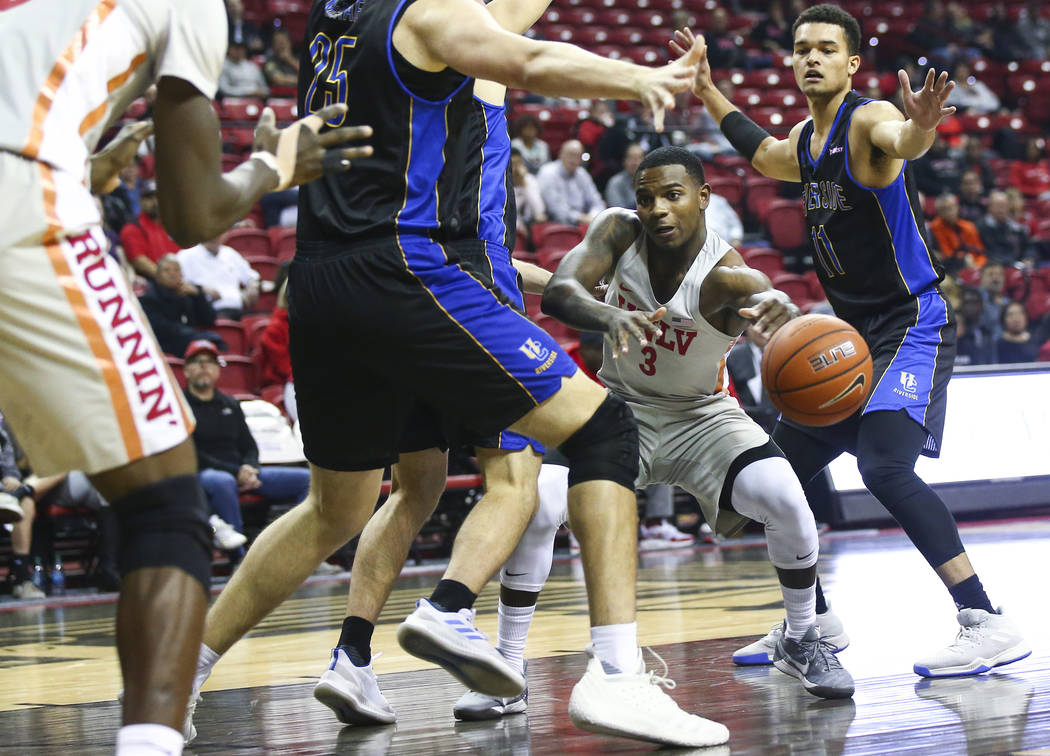 UNLV Rebels guard Amauri Hardy (3) passes the ball to UNLV Rebels forward Cheickna Dembele under pressure from UC Riverside Highlanders forward Zac Watson (11) during the first half of a basketbal ...