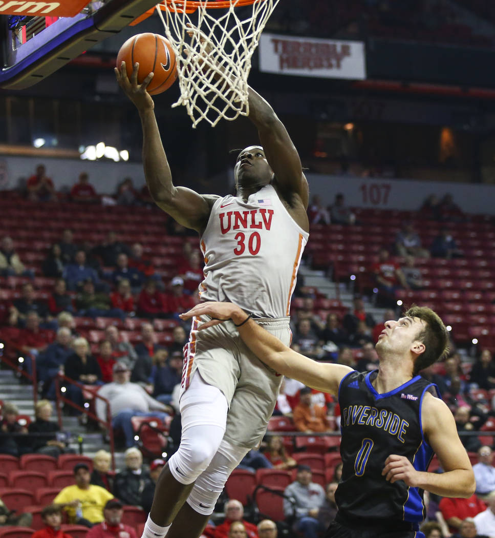UNLV Rebels forward Jonathan Tchamwa Tchatchoua (30) goes to the basket over UC Riverside Highlanders guard Dragan Elkaz (0) during the first half of a basketball game at the Thomas & Mack Cen ...