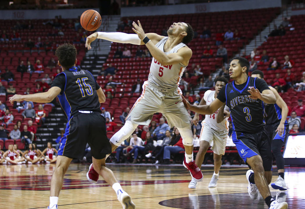 UNLV Rebels guard Noah Robotham (5) gets tripped up while throwing a pass in front of UC Riverside Highlanders guard DJ McDonald (3) during the second half of a basketball game at the Thomas & ...
