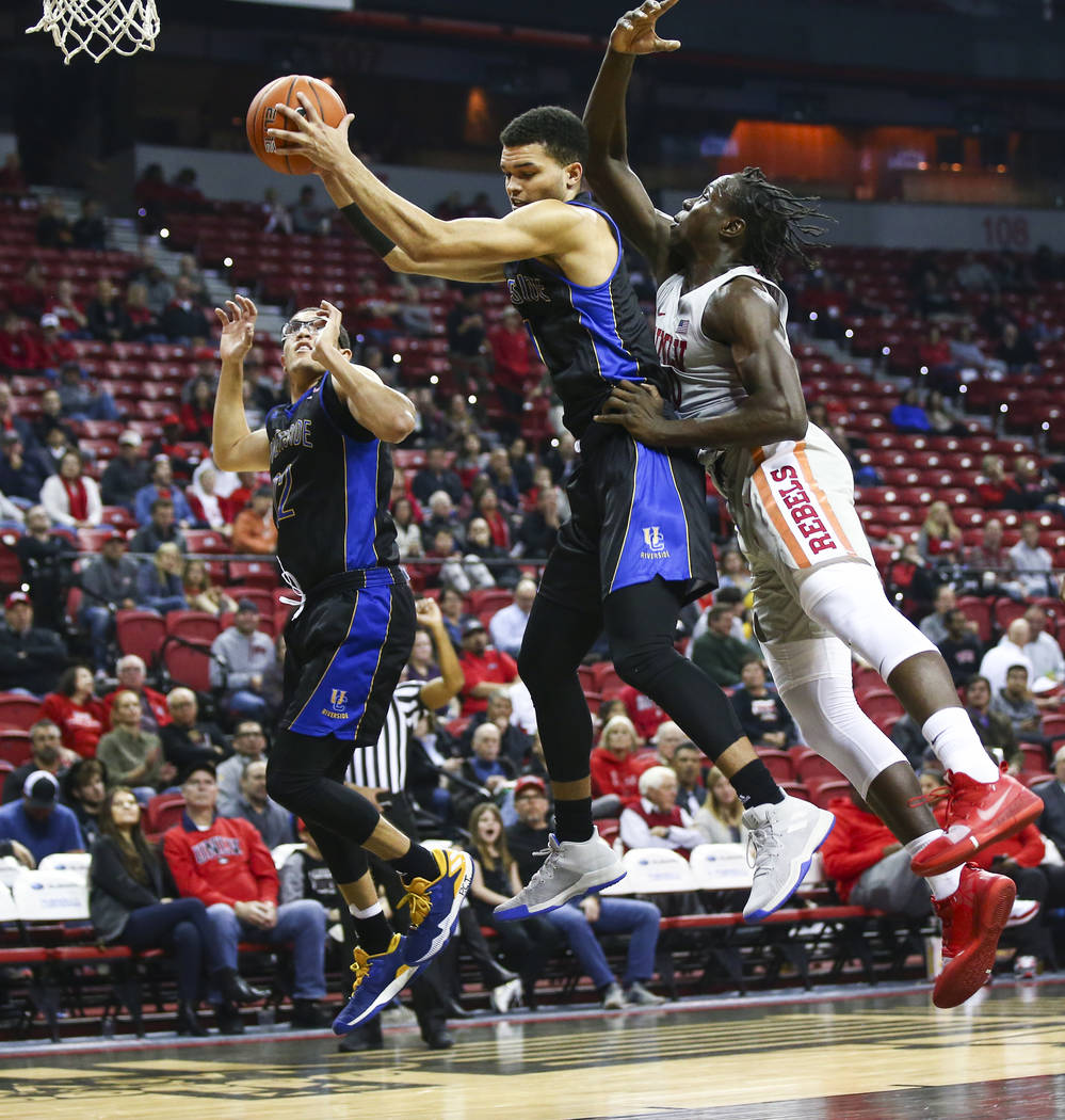 UC Riverside Highlanders forward Zac Watson (11) gets a rebound in front of UNLV Rebels forward Jonathan Tchamwa Tchatchoua (30) during the first half of a basketball game at the Thomas & Mack ...