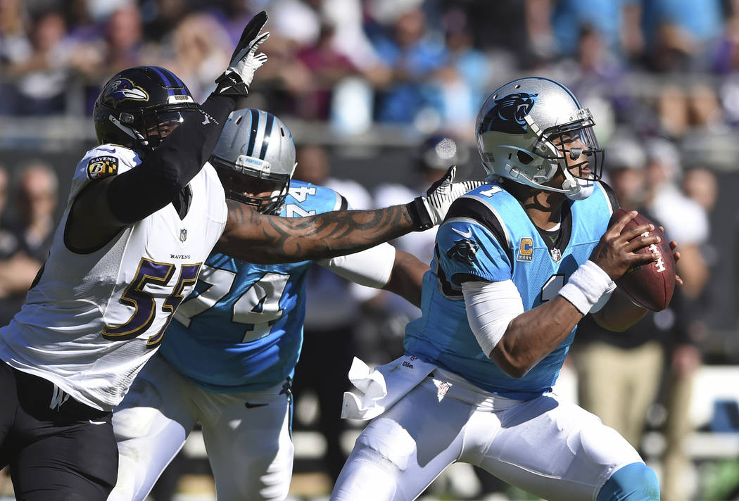 FILE - In this Oct. 28, 2018, file photo, Carolina Panthers' Cam Newton (1) looks to pass under pressure from Baltimore Ravens' Terrell Suggs (55) during the first half of an NFL football game in ...