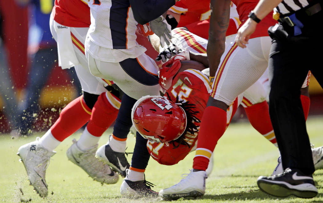 Kansas City Chiefs running back Kareem Hunt (27) lands into the end zone for a touchdown during the second half of an NFL football game against the Denver Broncos in Kansas City, Mo., Sunday, Oct. ...