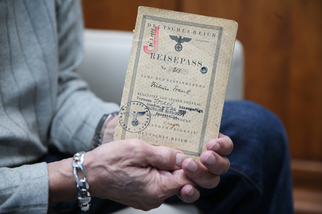 Joseph Frank, a Holocaust survivor, holds the passport issued to his father Julius Frank by the German government during the Holocaust, at his Henderson home, Wednesday, Oct. 31, 2018. The German ...