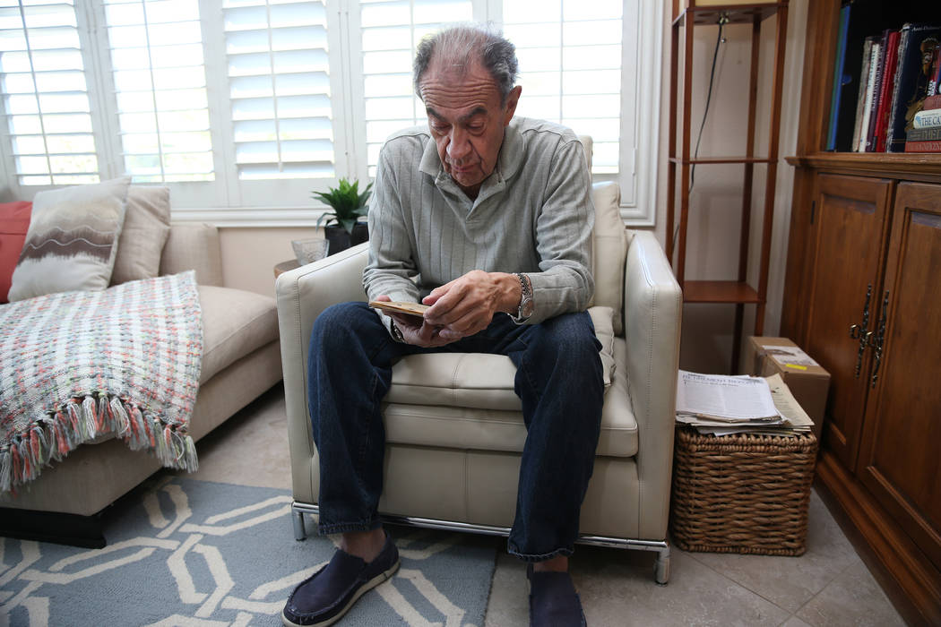Joseph Frank, a Holocaust survivor, looks at the passport issued to his father Julius Frank by the German government during the Holocaust, at his Henderson home, Wednesday, Oct. 31, 2018. Erik Ver ...