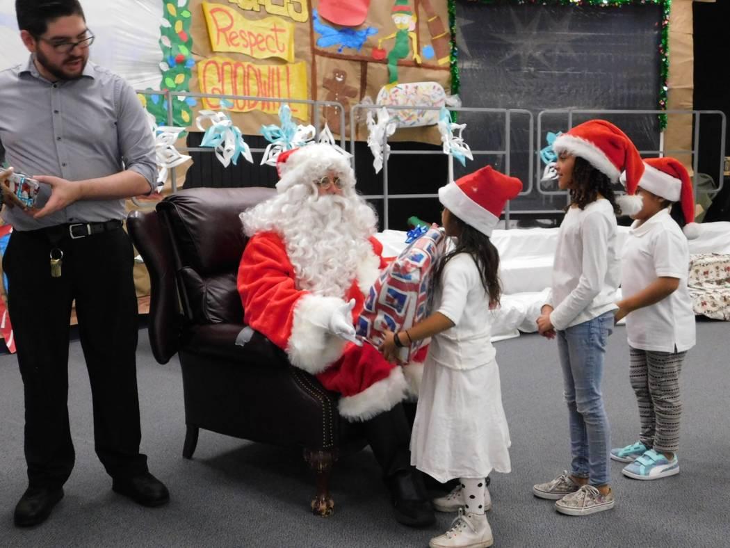 Santa Fe Station team members help Santa give children at Mabel Hoggard gifts.