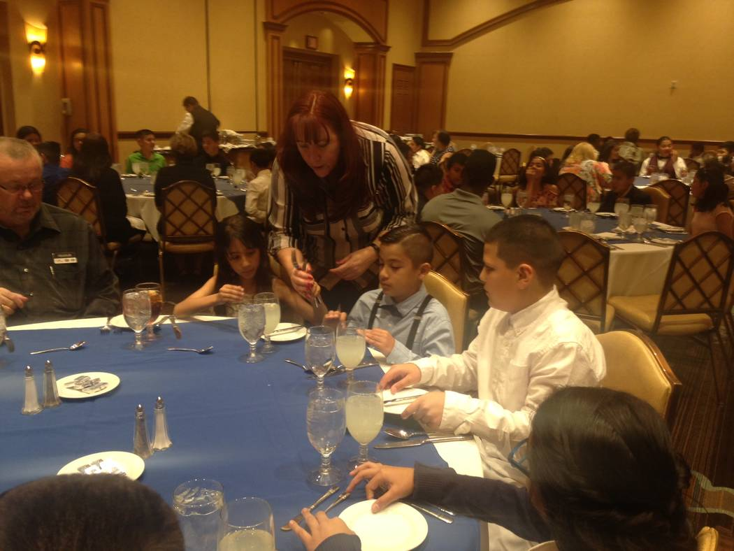 Texas Station's director of catering, Jen Cameron, helps students from CP Squires Elementary School during the annual fifth grade etiquette luncheon, which is held at the property to allow stude ...