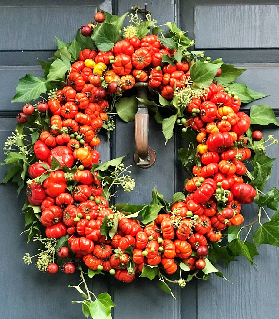 """Rose hips, berried green ivy and stems of bright orange """"pumpkin trees"""" are the components of a wreath dubbed Pumpkin Patch. (Laura Dowling/Stichting Kunstboek)"""