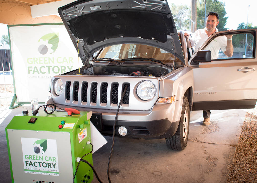 Jean-Luc Montagnier, co-owner of the Green Car Factory, uses hydrogen generator technology to clean an engine. (Tonya Harvey/Drive)