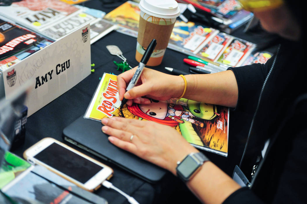 Amy Chu, right, a comic book writer who has written for Poison Ivy, Wonder Woman and Red Sonya, signs a comic for a fan at the 11th annual Vegas Valley Comic Book Festival at the Clark County Libr ...