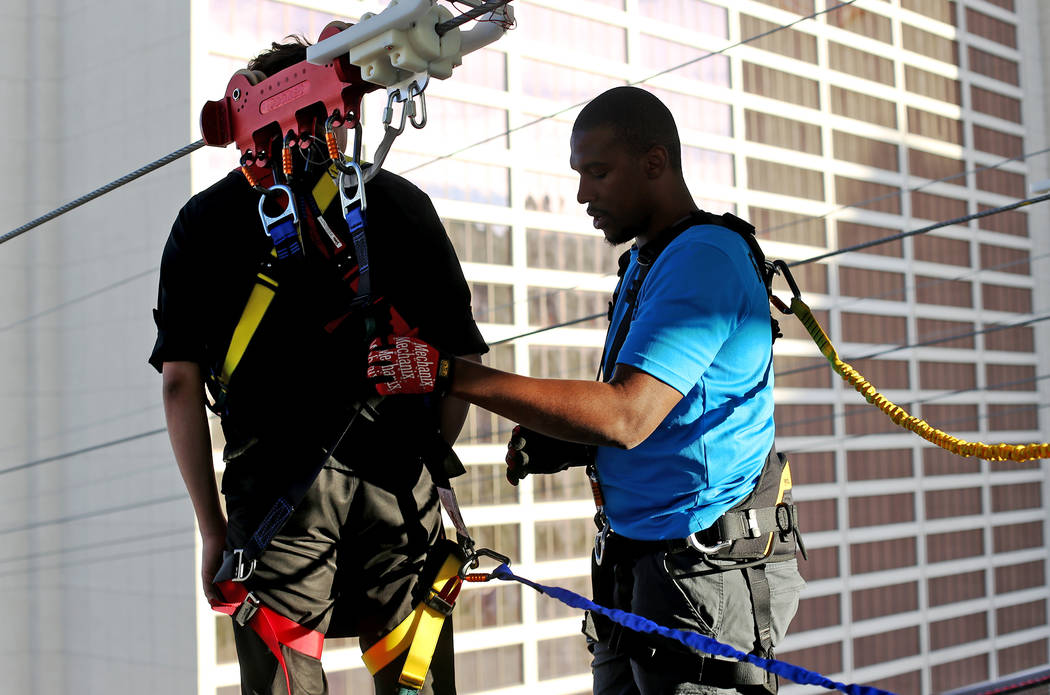 Jerome Barnes prepares a guest for the new Fly Linq Zipline at the Linq Hotel in Las Vegas, Thursday, Nov. 1, 2018. Participants start at the Strip, then fly over the Linq Promenade towards the Li ...