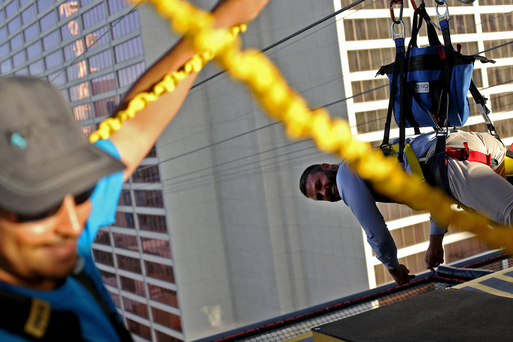 Julian Gonzales laughs with a guest before his flight at the new Fly Linq Zipline at the Linq Hotel in Las Vegas, Thursday, Nov. 1, 2018. Participants start at the Strip, then fly over the Linq Pr ...