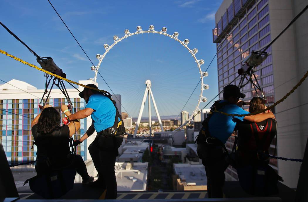 Workers Tyler Zimmer, left, and Julian Gonzales, right, prepare guests for the new Fly Linq Zipline at the Linq Hotel in Las Vegas, Thursday, Nov. 1, 2018. Participants start at the Strip, then fl ...