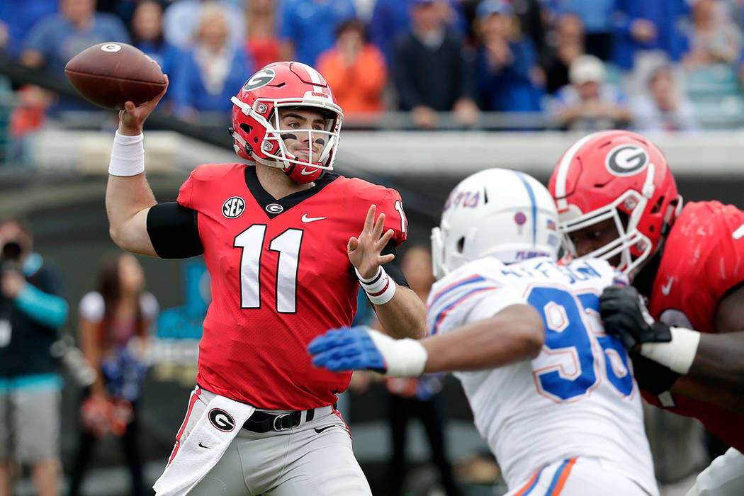Georgia quarterback Jake Fromm (11) looks to throw a pass as Florida defensive lineman Cece Jefferson, right, rushes during the first half of an NCAA college football game Saturday, Oct. 27, 2018, ...