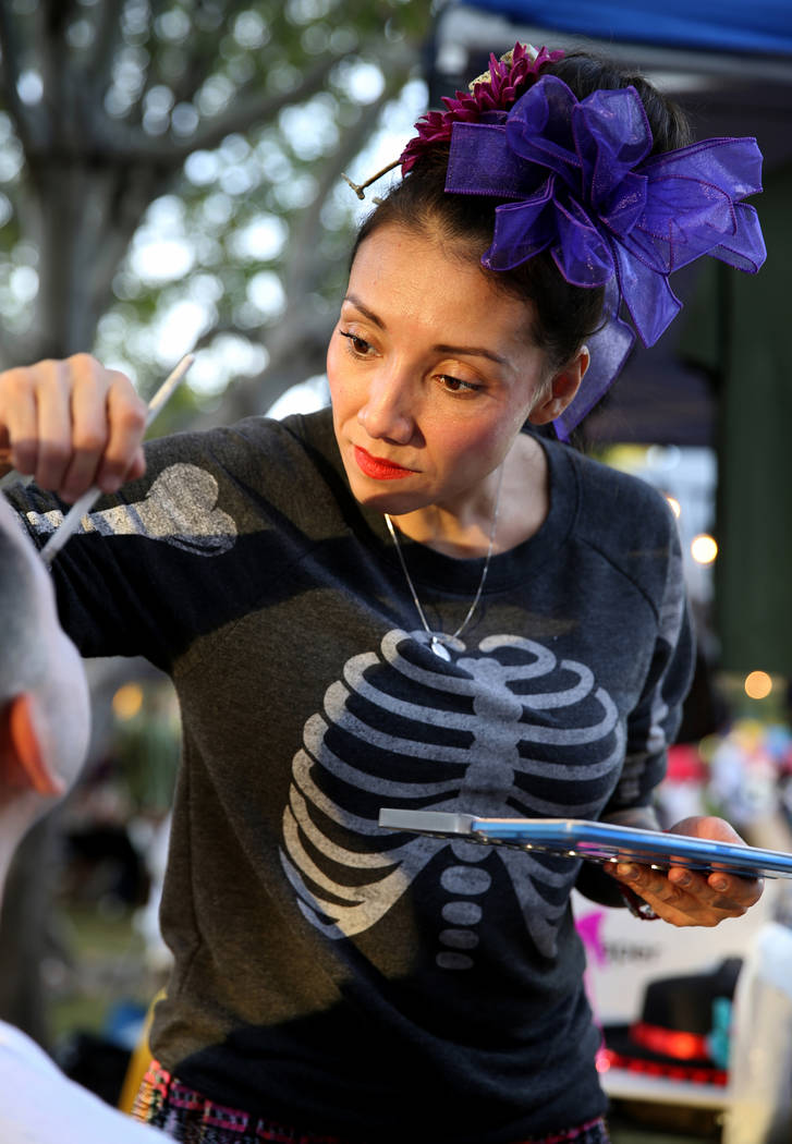 Brenda Occhipinti, whose 12-year-old son Carlo Jr. died from the flu, paints a friend's face during Life in Death: Day of the Dead Festival at Winchester Cultural Center in Las Vegas Friday, Nov. ...