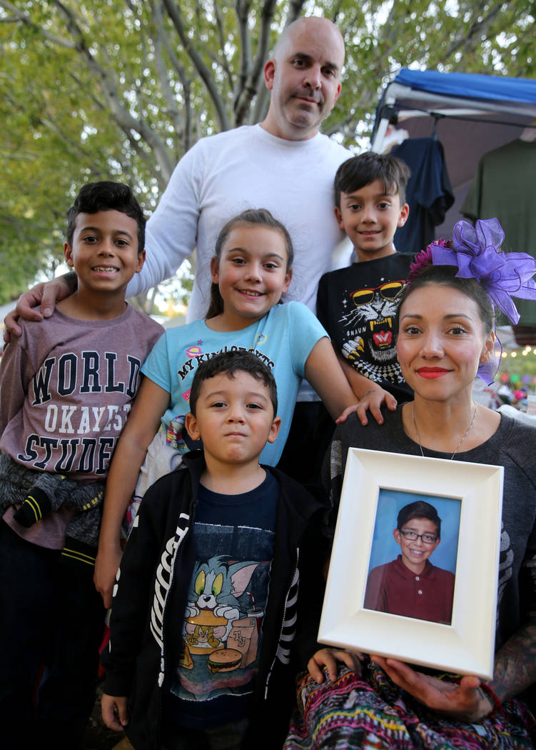 Brenda Occhipinti holds a photo Friday, Nov. 2, 2018, of her 12-year-old son Carlo Jr. who died in December from the flu. Occhipinti is with her children, from left, Marcelino, 8, Emiliano, 4, Isa ...